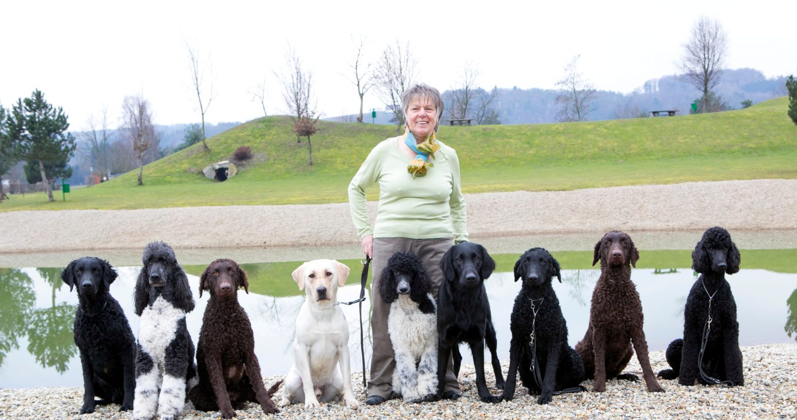 Trainer Maria Gerstmann with 9 sitting trainees by a lake