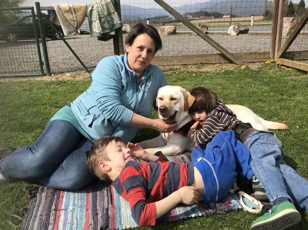 Autismus Begleithund mit seiner Familie. Mutter mit zwei Kindern und blonden Labrador.